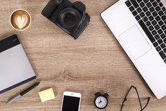 Photo blogger / photographer / it specialist`s typical office space table with laptop, blank screen, coffee cup and electronics. royalty free stock image