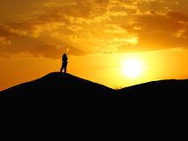 Photographer in the desert. Of Morocco with a beautiful dusk Royalty Free Stock Photography