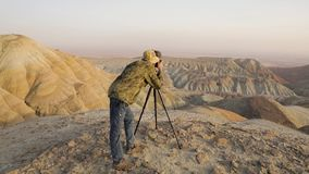 Photographer in the desert. Photographer with camera on tripod making photo of himself at surreal red mountains in the desert stock video
