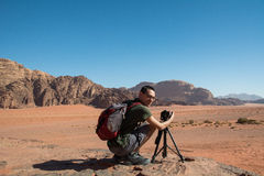 Photographer in the desert. With camera and tripod. Smiling Royalty Free Stock Images