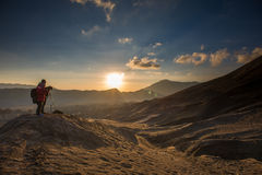 Photographer at a desert during Sunrise. Photographer photographing sunrise at Bromo Tengger Semeru National Park Stock Photo