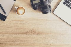 Photo blogger / photographer / it specialist`s typical office space table with laptop, blank screen, coffee cup and electronics. stock photo