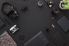Photographer desk with vintage cameras and modern technology. Black background. Top view with copy space. stock photo