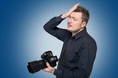 Photographer with digital camera, blue background Stock Photography