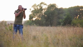 Photographer doing his job in the evening sun. stock footage