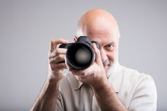 Photographer draw a bead on camera. Frontal portrait of a senior photographer aiming at you - on a gray background Royalty Free Stock Images