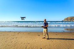Photographer with a drone on beautiful beach Royalty Free Stock Image