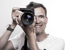 Photographer with DSLR camera. Paparazzi photographer takes a photo while smiling at you stock photography