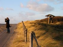 Photographer in Dunes. Woman taking photographs at sunset on a winter day in the dunes near Monster, Netherlands Royalty Free Stock Image