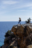 Photographer enjoying seaview and standing on high rock cliff. Blond woman photographer enjoying seaview and standing on high rock cliff portrait layout Stock Photo