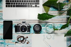 Photographer equipment collected on vintage table. Photographer equipment - laptop, vintage style DSLR camera, lens, graphics tablet and smartphone with some Royalty Free Stock Images