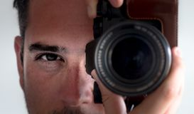 Photographer eye contact camera viewfinder. Man closeup stock image