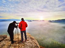 Photographer  with eye at viewfinder of camera on tripod stay on cliff and takes photos, talk friends. Autumn beautiful  misty landscape, misty sunrise  at Stock Images