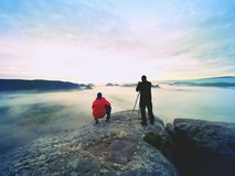 Photographer  with eye at viewfinder of camera on tripod stay on cliff and takes photos, talk friends. Autumn beautiful  misty landscape, misty sunrise  at Stock Image