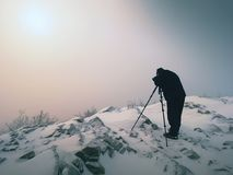 Photographer with eye at viewfinder of camera on tripod stay on snowy cliff and takes photos. Winter beautiful misty landscape, sunrise hidden in thick fog Royalty Free Stock Photography