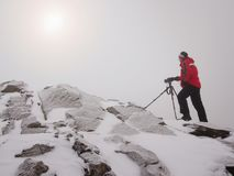 Photographer with eye at viewfinder of camera on tripod stay on snowy cliff and takes photos. Winter beautiful misty landscape, sunrise hidden in thick fog Royalty Free Stock Photos