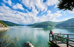 Photographer female on the lake Vidraru Carpathians Romania. Beautiful scenery of a sunny day: mountains, forests, lake, blue sky with clouds Royalty Free Stock Photos