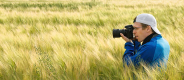 Photographer in a field of barley stock photo