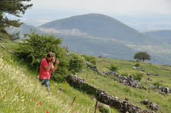 Photographer on the flowering slope in spring mountains Royalty Free Stock Image