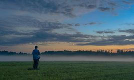Photographer in a fog field. Latvian sunset of fog and blue sky - romantic evening Stock Photo