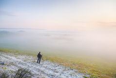 The photographer in a fog in mountains Stock Photos