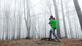 Photographer in foggy forest. Dark scary forest like a fairy tale Stock Image