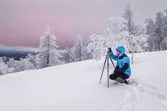 Photographer in foggy winter landscape with tripod stock photo