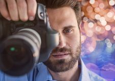 Photographer foreground taking a photo with reflex. Blurred  brown and blue lights background and ov Royalty Free Stock Images