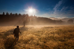 Photographer in forest with fog looking for adventure Stock Images