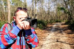 Photographer in the forest photographing the natural environment. Photographer in the forest. Guys in nature photography forest environment, enjoying the Stock Photography