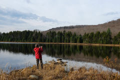 Photographer at G Lake. Female photographer holding camera at G Lake in the Adirondack Park in early winter Royalty Free Stock Images
