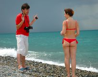 The photographer and girl. The photographer take pictures a model in red bikini on a beach Stock Photos
