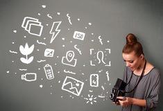 Photographer girl capturing white photography icons and symbols. Young photographer girl capturing white photography icons and symbols Royalty Free Stock Image