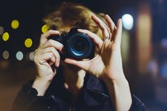 Photographer girl enjoying night street in trip, traveler relax lifestyle concept, hipster hiker tourist making photo, holding in Royalty Free Stock Photography