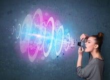 Photographer girl making photos with powerful light beam Stock Image