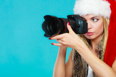 Photographer girl in santa claus hat shooting images Royalty Free Stock Image