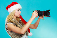 Photographer girl in santa claus hat shooting images Royalty Free Stock Images