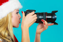 Photographer girl in santa claus hat shooting images Stock Image