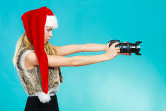 Photographer girl in santa claus hat shooting images Royalty Free Stock Photography
