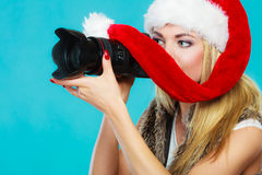 Photographer girl in santa claus hat shooting images Royalty Free Stock Photo