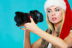 Photographer girl in santa claus hat shooting images Stock Photo