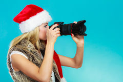 Photographer girl in santa claus hat shooting images Stock Photography