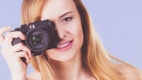 Blonde woman with camera on blue royalty free stock photo