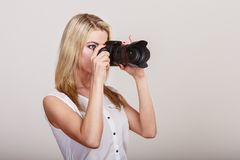 Photographer girl shooting images. Attractive blonde woman taking photos with camera royalty free stock image