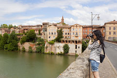 Photographer girl taking a photograph from Old bridge in Albi Stock Images
