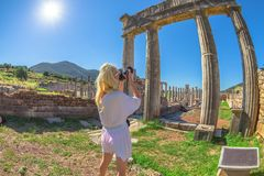 Photographer in Greek Travel. Travel photographer with reflex at woman Doric Propylon in Ancient Messene, Historical columns, Peloponnese, Greece. Seductive stock photos