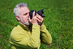 Photographer on green grass. Holding camera Royalty Free Stock Image