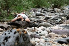 Photographer. The guy lies on stones and photographs royalty free stock images