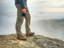 Photographer hand with camera, legs, knees and boots. Man takes photos. Photographer hand with camera, legs, knees and boots. Man takes landscape photos on peak stock image