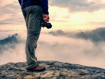 Photographer hand with camera, legs, knees and boots. Man takes photos. Photographer hand with camera, legs, knees and boots. Man takes landscape photos on peak stock photos